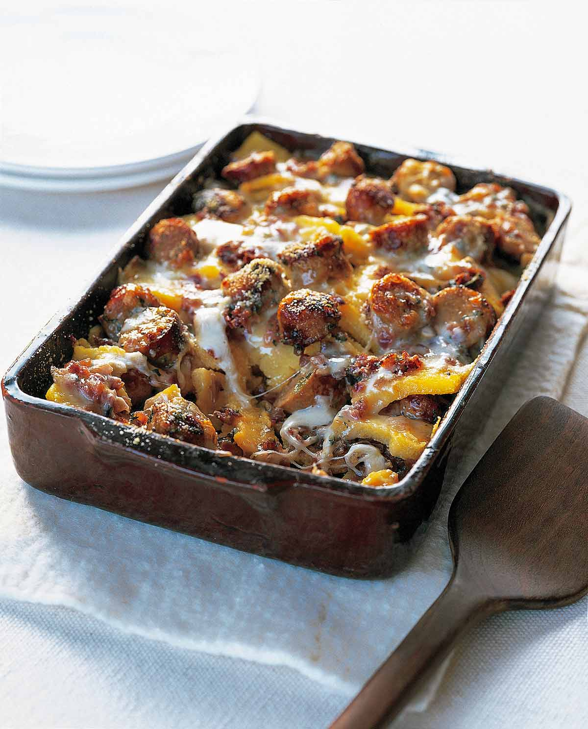 A rectangular casserole dish filled with baked polenta with sausage and cheese.