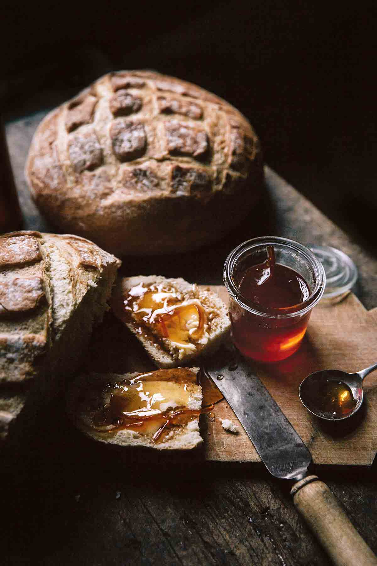 Two loaves of artisan bread and a jar of Campari citrus marmalade, with a slice of bread smeared with the marmalade on a wooden cutting board.