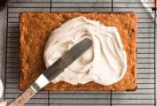 A whole carrot sheet cake on a wire rack with chai cream cheese frosting being spread over the top.