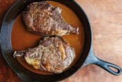 Two cowboy steaks in a cast-iron skillet with a Guinness sauce.
