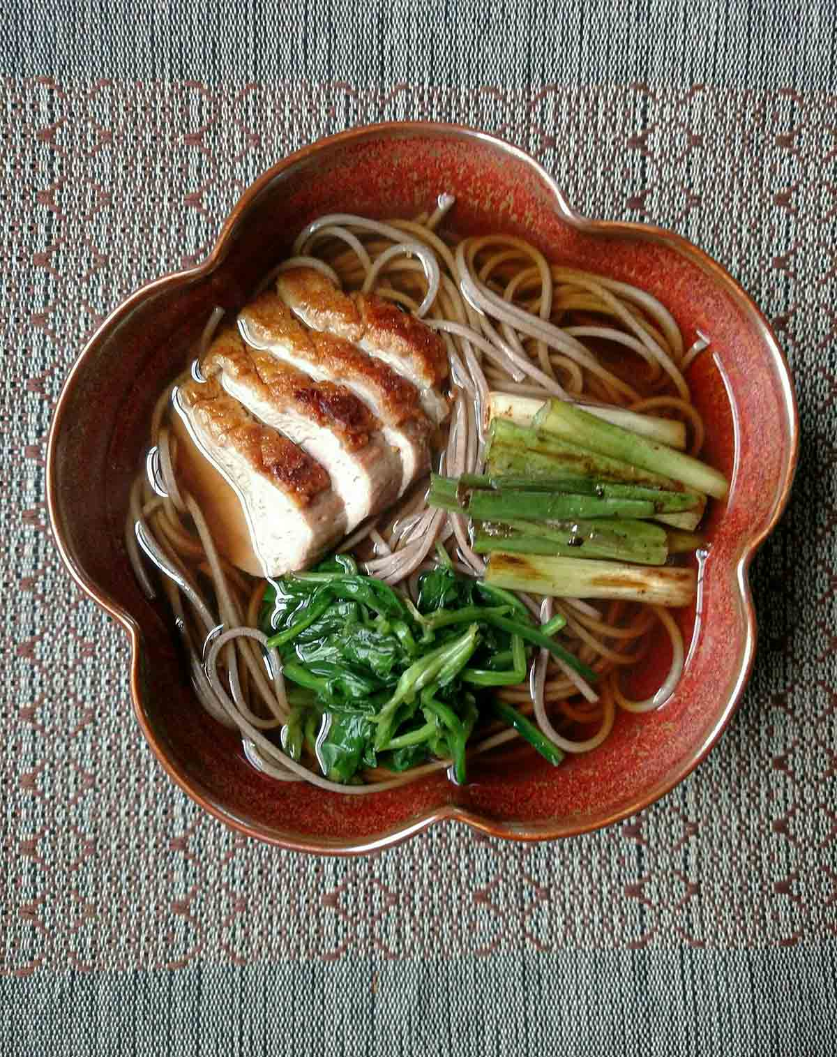 A bowl filled with duck soba, seasoned spinach, and scallions.