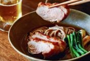 A bowl of duck soba with scallions on a wooden surface with a piece of duck being lifted out with chopsticks.