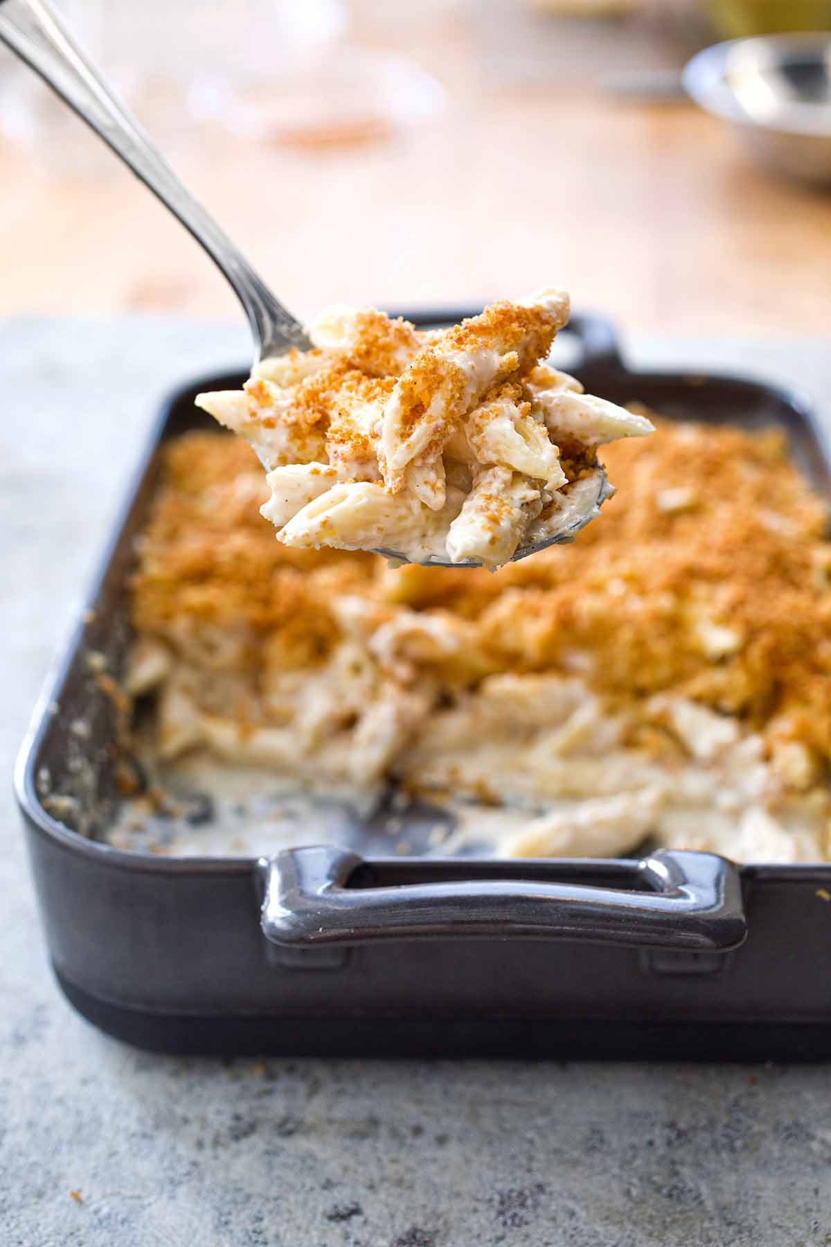 A dark grey rectangular baking dish half filled with four cheese macaroni and cheese and a metal spoon lifting a scoop out.
