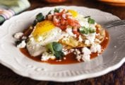 A white plate topped with huevos rancheros - crispy tortilla, fried eggs, fresh salsa, and Cotija cheese.