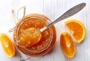 A jar of orange marmalade with a spoon resting on top and a few orange wedges beside it.