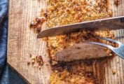 A panko crusted pork tenderloin with rosemary being sliced on a wooden cutting board.