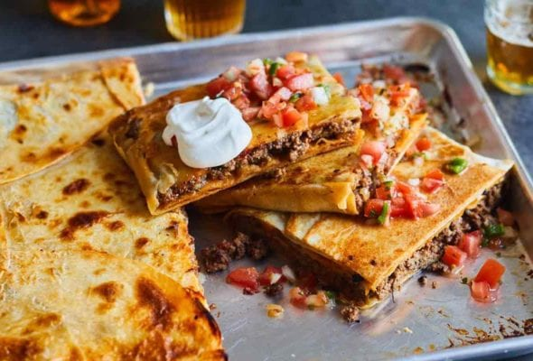 A cut sheet pan taco bake in a rimmed sheet pan topped with pico de gallo and sour cream.