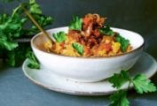 A bowl filled with spicy harissa lentil stew on a white plate with flat leaf parsley garnishing the dish and scattered around the bowl.