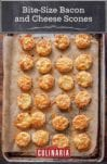 Bite-size bacon and cheese scones with smoked bacon and melted Asiago on top on a parchment-lined baking sheet