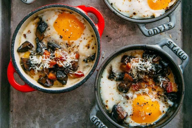 Four individual cocottes filled with baked eggs with polenta and mushrooms on a rimmed baking sheet.