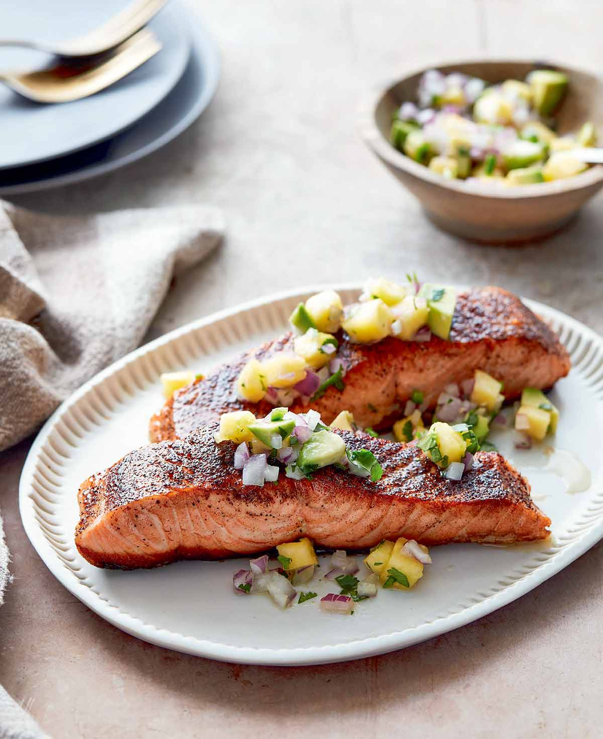 Two pieces of blackened salmon topped with pineapple salsa on an oval serving plate.