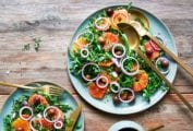 A large platter and smaller plate topped with blood orange and arugula salad with a dish of black olives on the side.