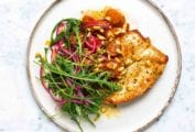 A white plate topped with a piece of brown butter flattened chicken, tomato sauce, arugula and red onion salad, and pine nuts.