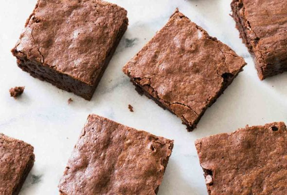 Squares of chocolate chip brownies on a white marble surface.