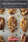 Nine crispy smashed potatoes with herbs on a baking sheet.