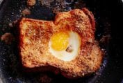 A slice of toast in a skillet with an egg in the hole of the toast.
