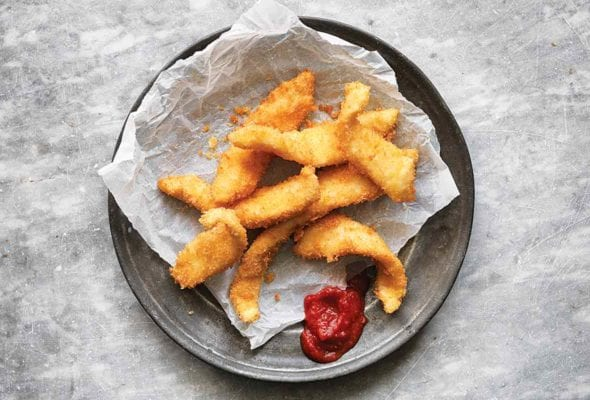 A pile of fancy fish sticks on a piece of parchment with a dollop of ketchup beside them.