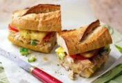 A halved fancy tuna melt with tomato and cucumber on a baguette on a piece of parchment.