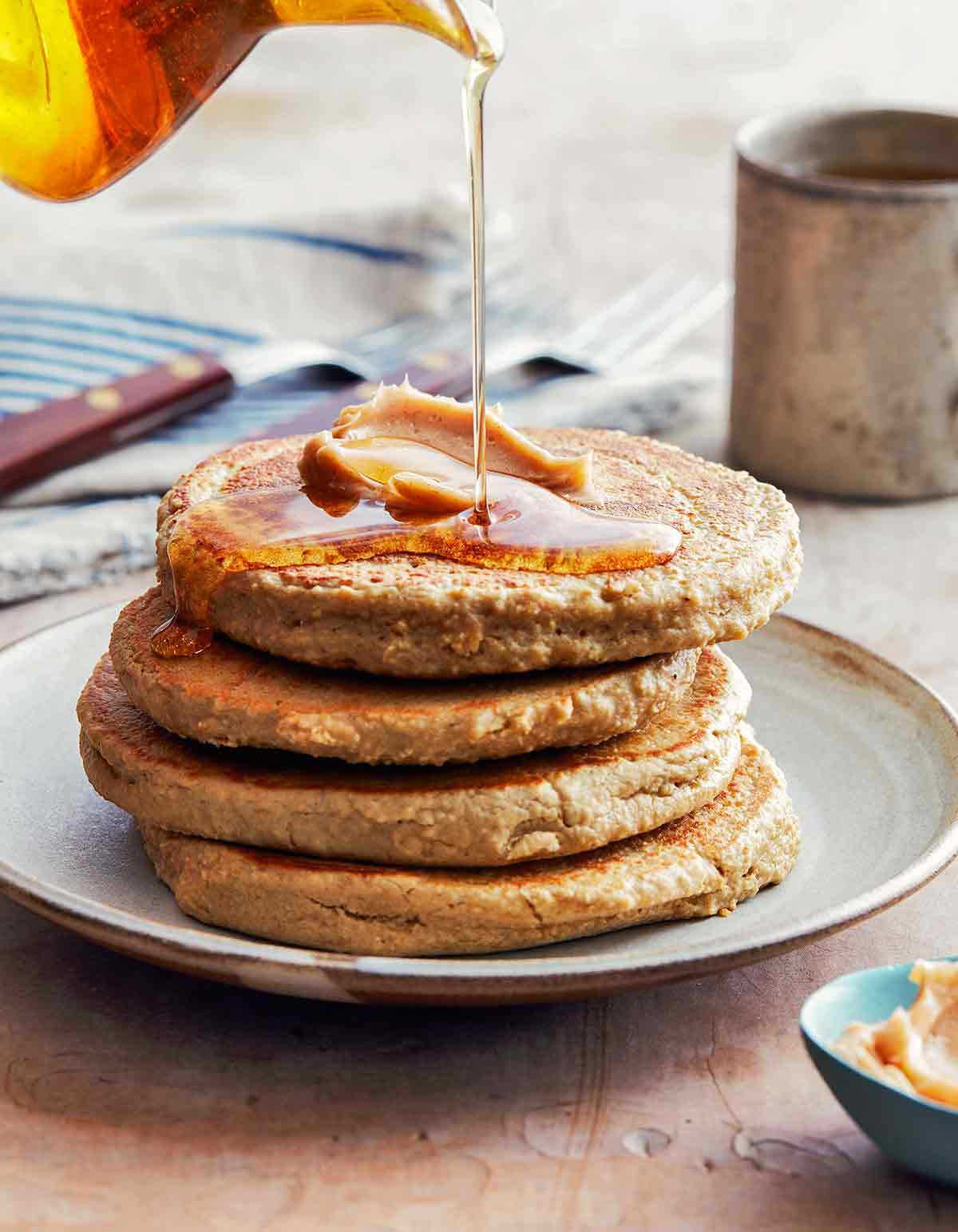 A stack of four gluten-free banana oat pancakes with syrup being poured over the top.