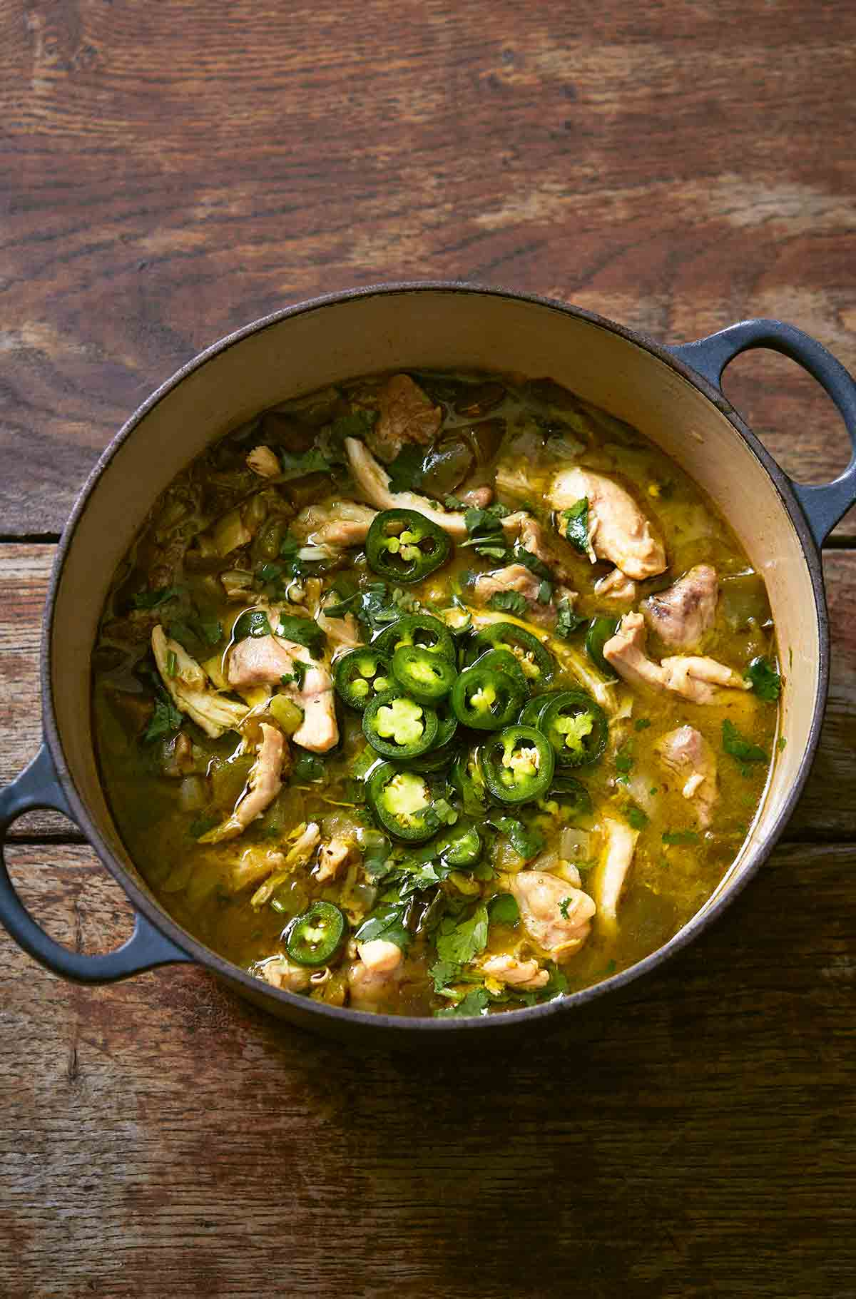 A large blue Dutch oven filled with green chicken chili, topped with sliced jalapenos.