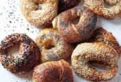 A variety of homemade bagels on a white surface.