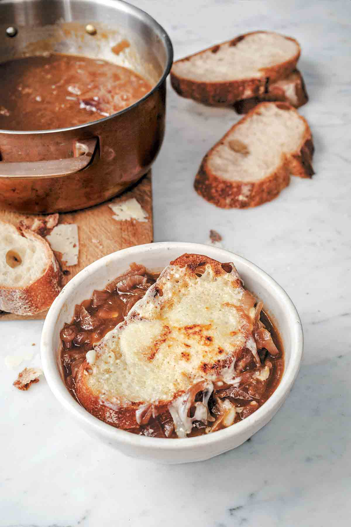 A white bowl of Italian onion soup topped with cheese toast with a pot of soup and several bread slices in the background.