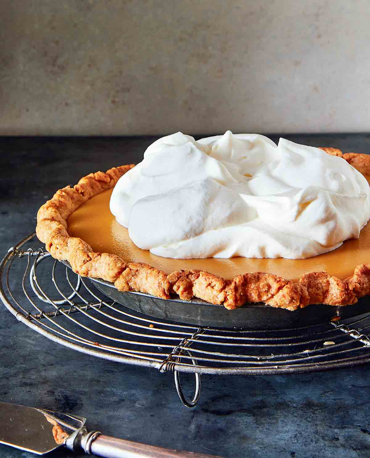 A whole maple cream pie, topped with whipped cream on a round wire rack.
