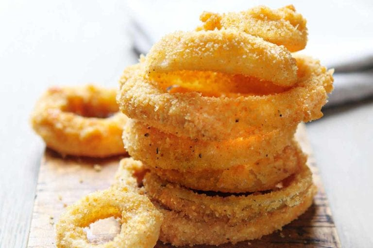 A stack of moonshine onion rings on a wooden board.