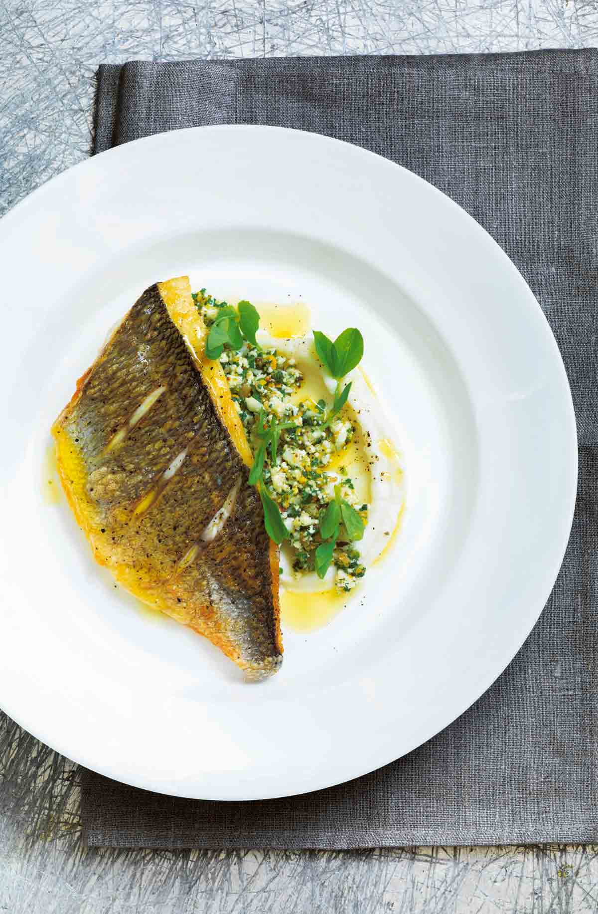 """A piece of pan-fried fish on top of cauliflower """"couscous"""" and cauliflower puree on a white plate."""