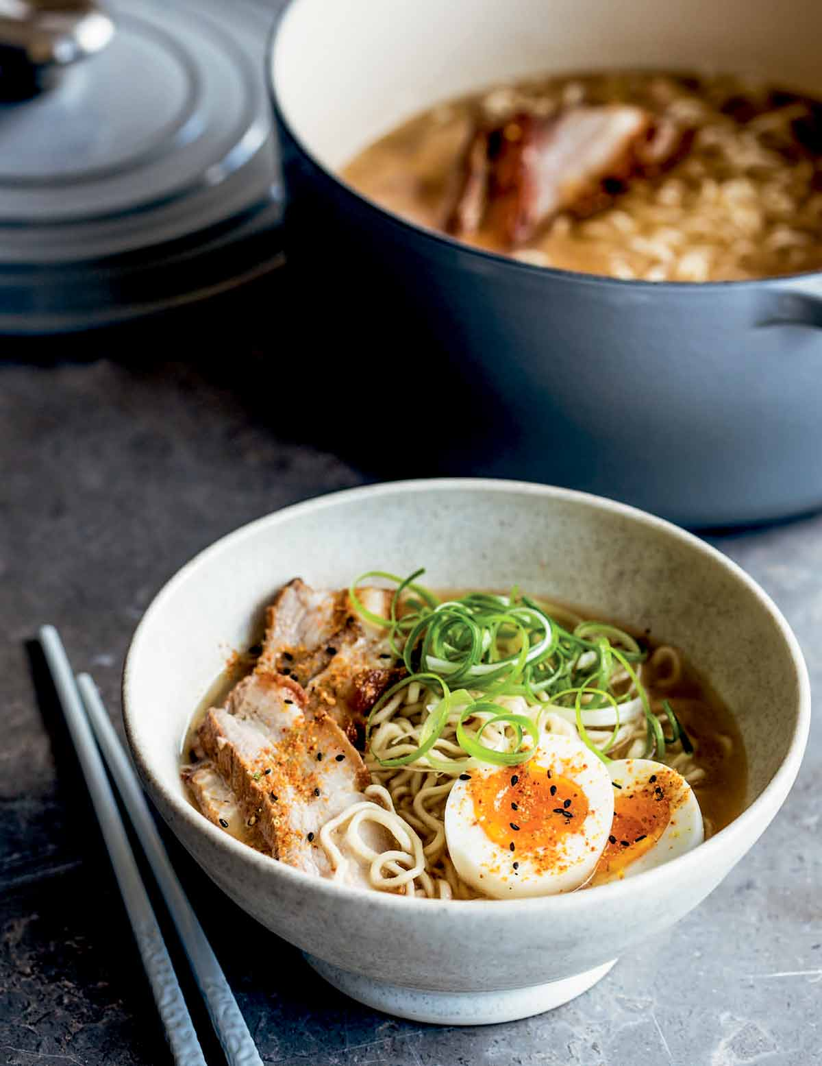 A white bowl filled with pork belly ramen, two egg halves, and scallions with a Dutch oven in the background and a pair of chopsticks lying beside the bowl.