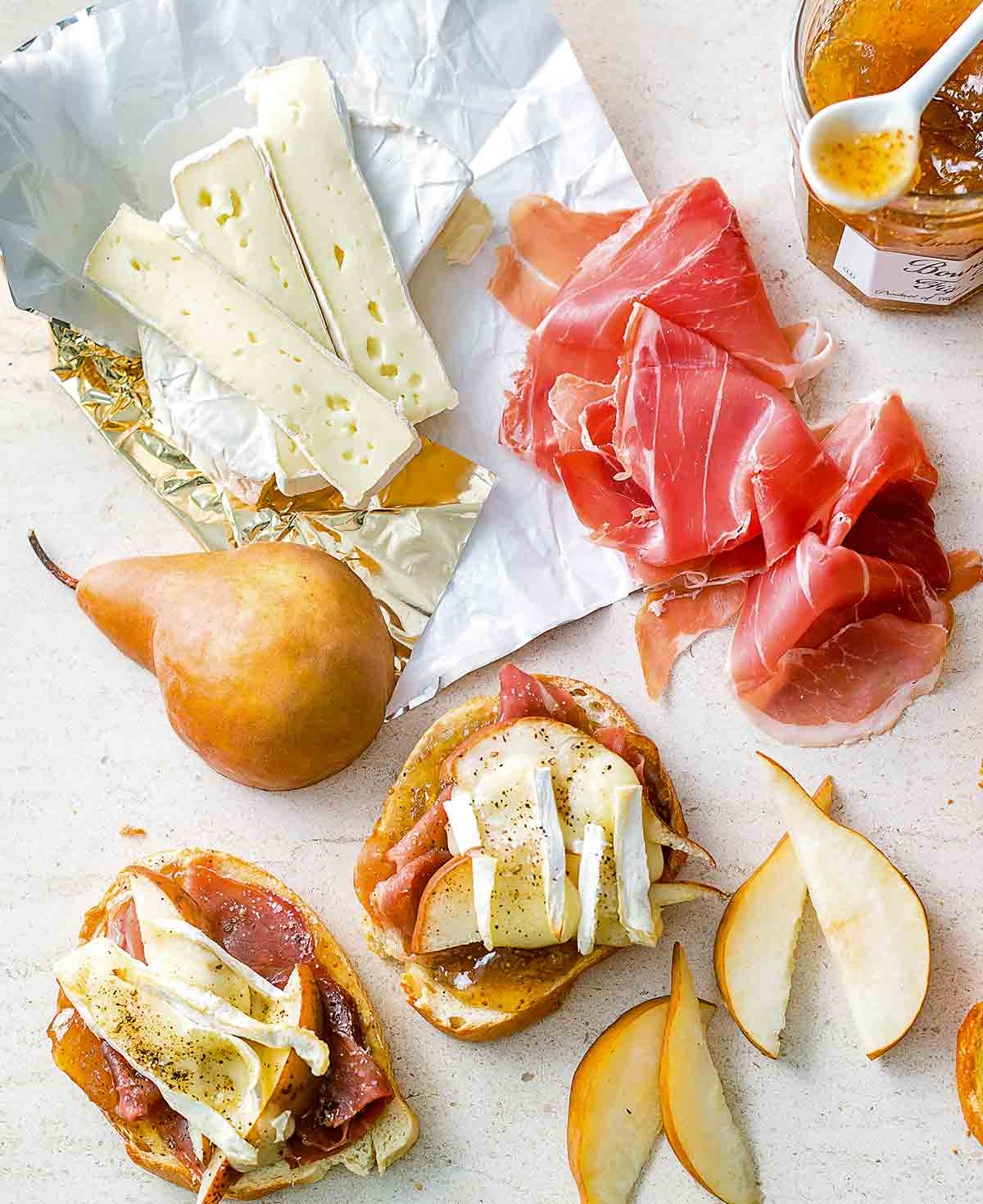 Two pieces of prosciutto, pear, and Brie toasts with slices of Brie, pear, prosciutto, and a jar of fig jam beside the toasts.