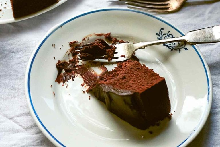 A partial slice of red wine chocolate cake on a plate with a fork resting beside the cake.