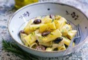 Bowl of rigatoni with artichokes, garlic, and olives, with lemon zest on a textured table