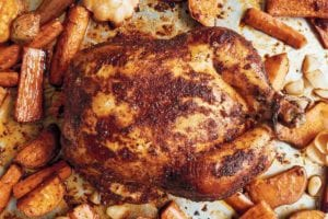 A whole roast chicken rubbed with paprika on a baking sheet with carrots and sweet potatoes.