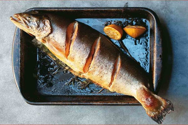 A whole salmon with roasted dill sauce and lemon halves on a metal baking tray.