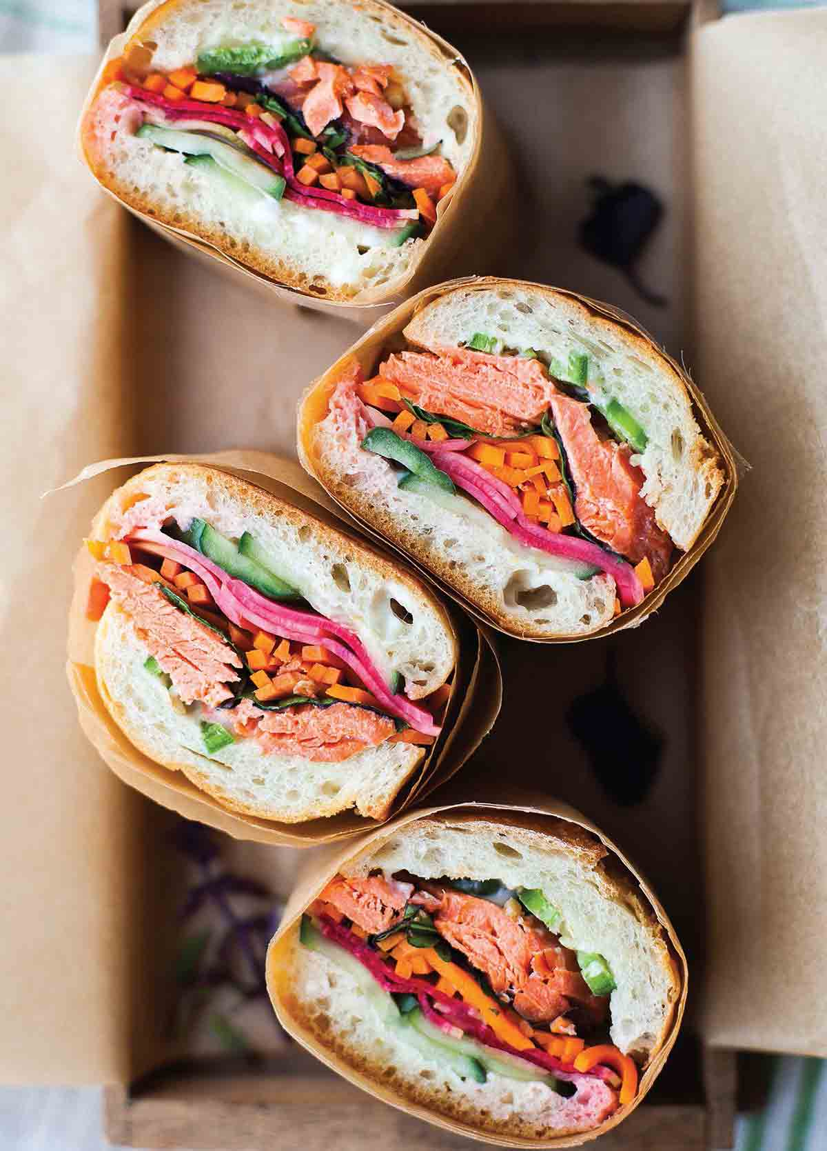 Four pieces of salmon banh mi wrapped in paper in a box.