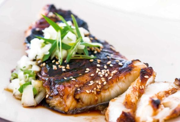 A piece of sea bass topped with soy glaze and cucumber salsa on a square shaped white plate.