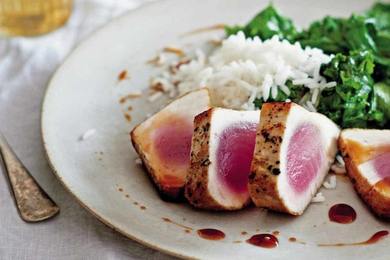 A white plate with four slices of seared tuna with sweet and sour sauce, rice, and cooked greens.