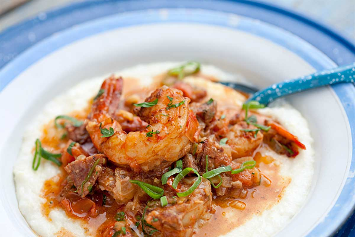 A blue and white bowl filled with shrimp and grits.