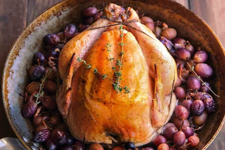 A whole simple roast chicken in a skillet, surrounded by grapes.