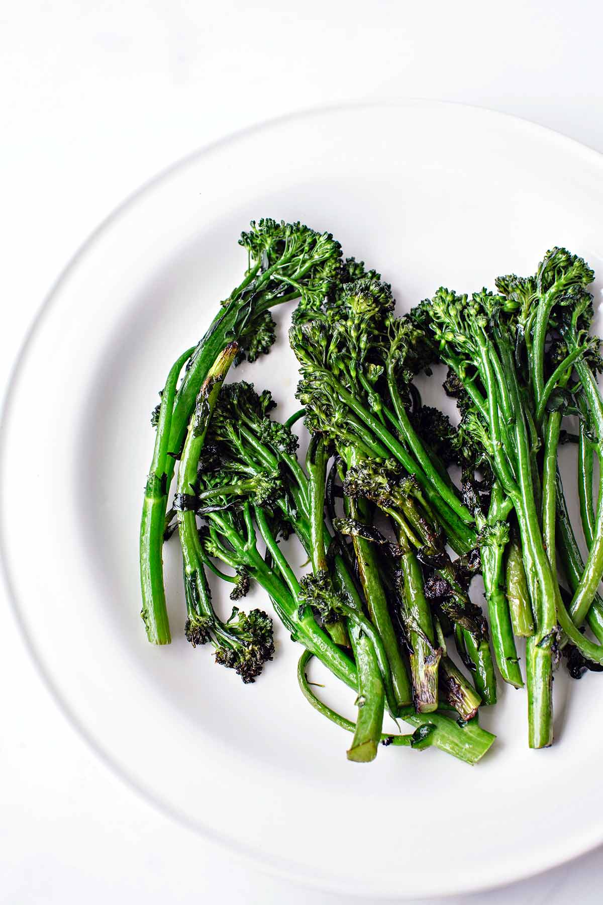 A white plate of skillet-charred broccolini.