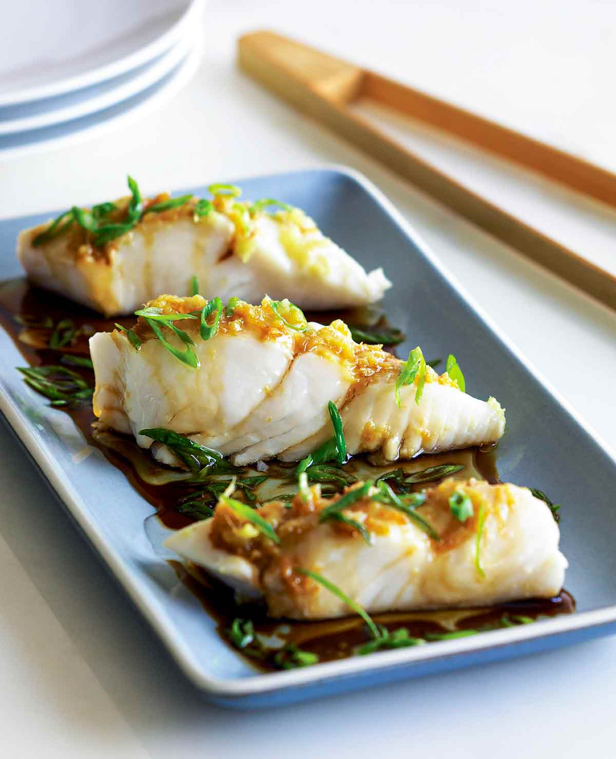 Three pieces of steamed halibut with ginger and scallions on a blue rectangular plate with chopsticks on the side.