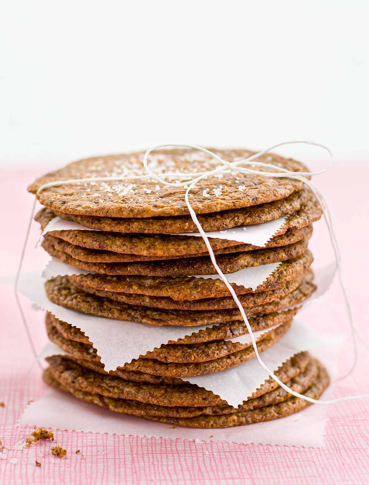 A stack of thin and crisp chocolate chip cookies with pieces of parchment in between, tied up with string and a glass bottle of milk in the background.