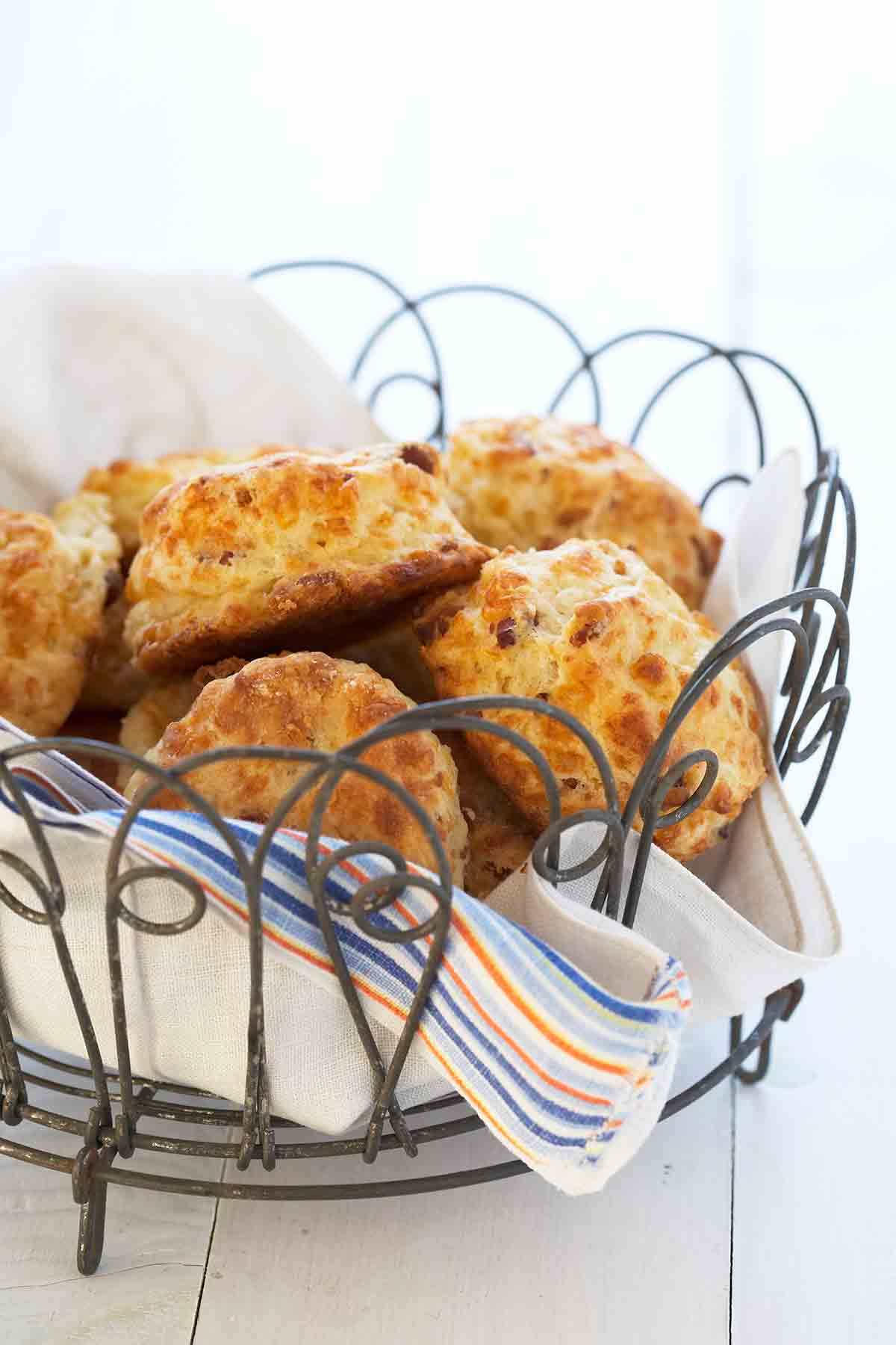 A wire basket lined with a napkin and filled with bacon Cheddar biscuits.