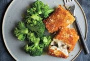 Two pieces of breaded fish fillets sprinkled with salt on a grey plate with a portion of steamed broccoli and a fork.
