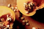 A halved butternut squash with the seeds partially scooped out to demonstrate how to waste less food.