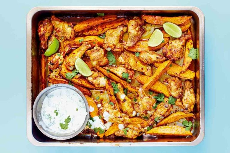 A metal tray filled with chipotle chicken wings, sweet potato wedges, and a Greek yogurt dipping sauce with lime wedges and cilantro leaves.