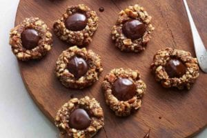 Nine chocolate thumbprint cookies and a chocolate covered spoon on a round wooden board.