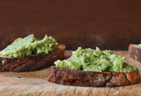 Three pieces of bread topped with fava bean puree.
