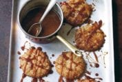 Six ginger-chile caramel cookies on a rimmed baking sheet drizzled with caramel sauce and a pot of caramel sauce.